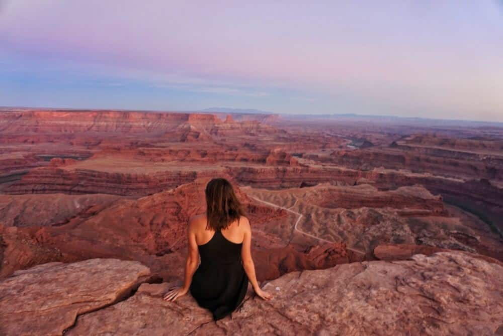 A back view of a seated woman looking out over the red rocks of Dead Horse Point State Park in UT