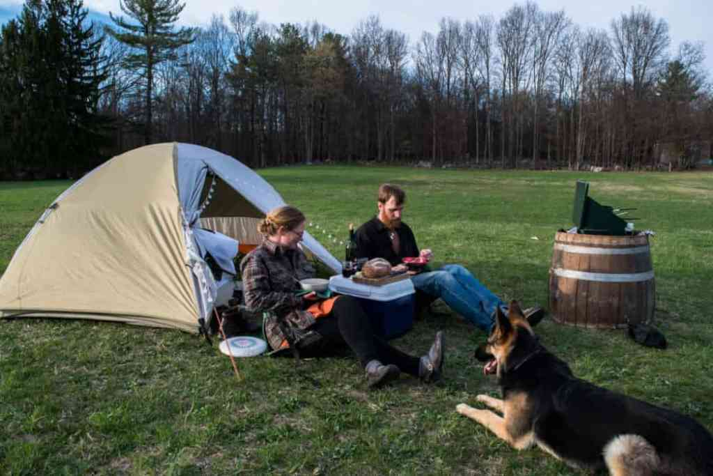 two people and a German Shepherd sitting in front of a small tent eating a meal.