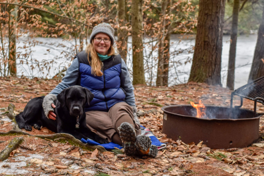 The author sits outside next to a campfire and a black lab dog.