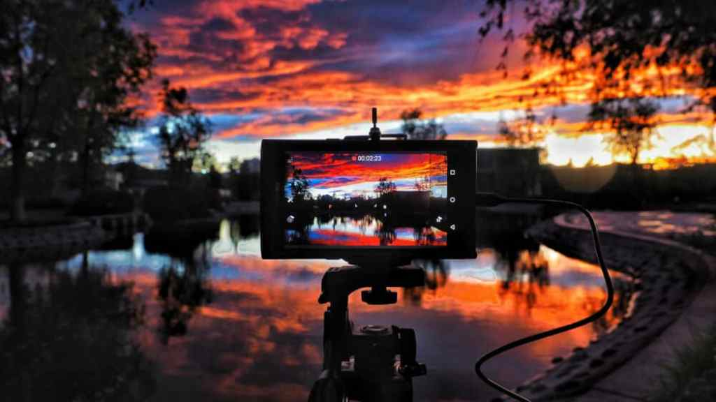 A colorful sunset over a lake with the LCD screen of a DSLR camera in the foreground.