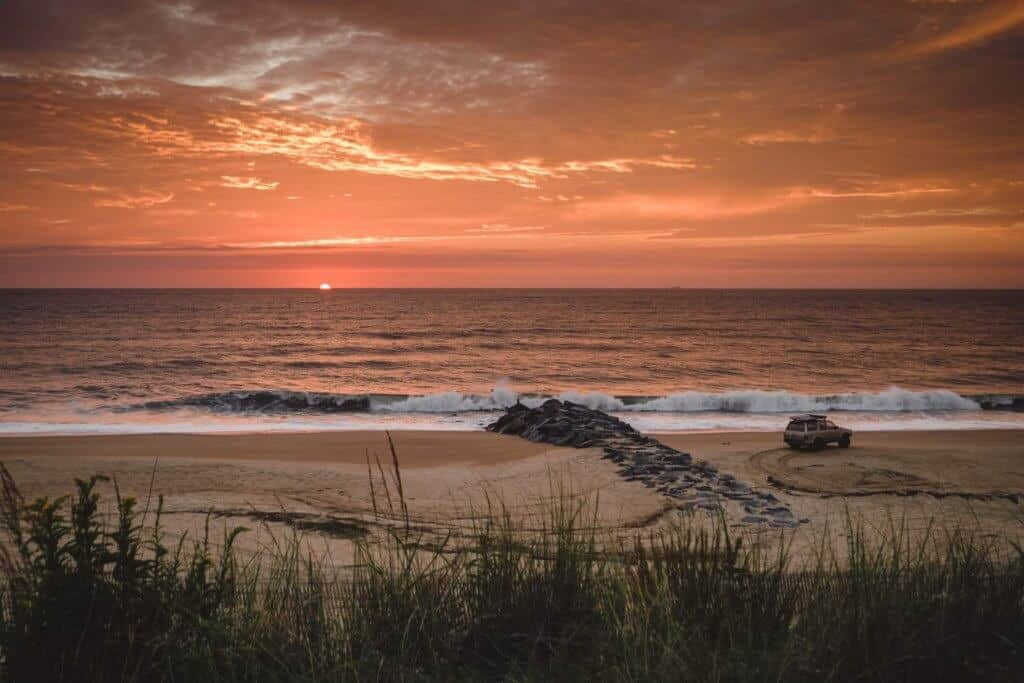 Best winter road trips - A car parked on the beach and a beautiful sunset.