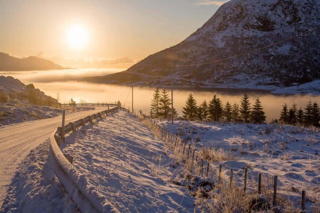 A snow covered road near a misty lake.