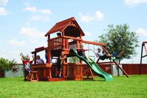 Children play on a Backyard Fun Factory Fort Davis style redwood swing set with a 5 foot deck height, 4.5 by 4.5 foot deck platform, and decorative sunbursts in the gables. This set has a lemonade stand, swings, and a bumpy slide.