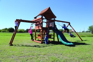 Children play on a Backyard Fun Factory Fun Shack redwood swing set that features a 5 foot deck height, sloped roof, rope ladder, swings, monkey bars, slide, and picnic table.