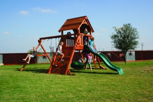 Children play on one of our Backyard Fun Factory Fort Concho style redwood swing sets with regular swings, a tire swing, a slide, and a rock climbing wall.
