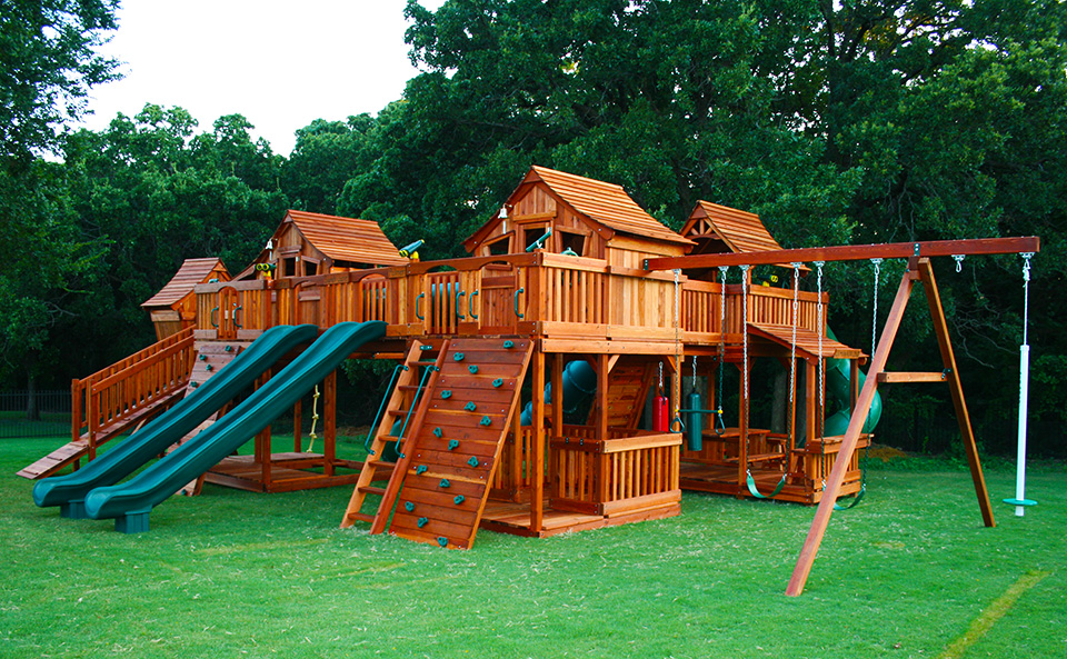 A picture of a couple of Backyard Fun Factory Fort Stockton Redwood  Playsets bridged to a - Why Redwood Swing Sets? Backyard Fun Factory