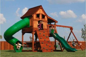 Children play on a Backyard Fun Factory Maverick style redwood swing set. This set features a 6 foot tall deck height, two slides, swings, a picnic table, a climbing wall, and a fort on top.