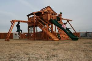 fort stockton, cabin, rock wall, ramp, monkey bars, wooden swing set, swing set, swings, slide, swing set for kids, kids, children, play, playground, playset, sets, accessories, backyard swing set