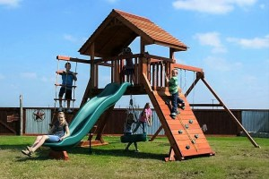 Children play on the Backyard Fun Factory Ranchero style redwood swing set. It features a straight roof, 6 foot high deck, climbing wall, slide, swings, rope ladder, and tire swing underneath.