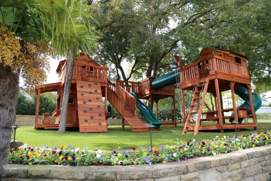 Fort Stockton playsets bridged to tree deck. Tree deck connected to outdoor swing set and fort with crawl tube. Bridge has a slide and boardwalk attached with monkey bars under the bridge. Kids lemonade stand, rock wall, spiral slides, and swings accessorized this wooden swing set.