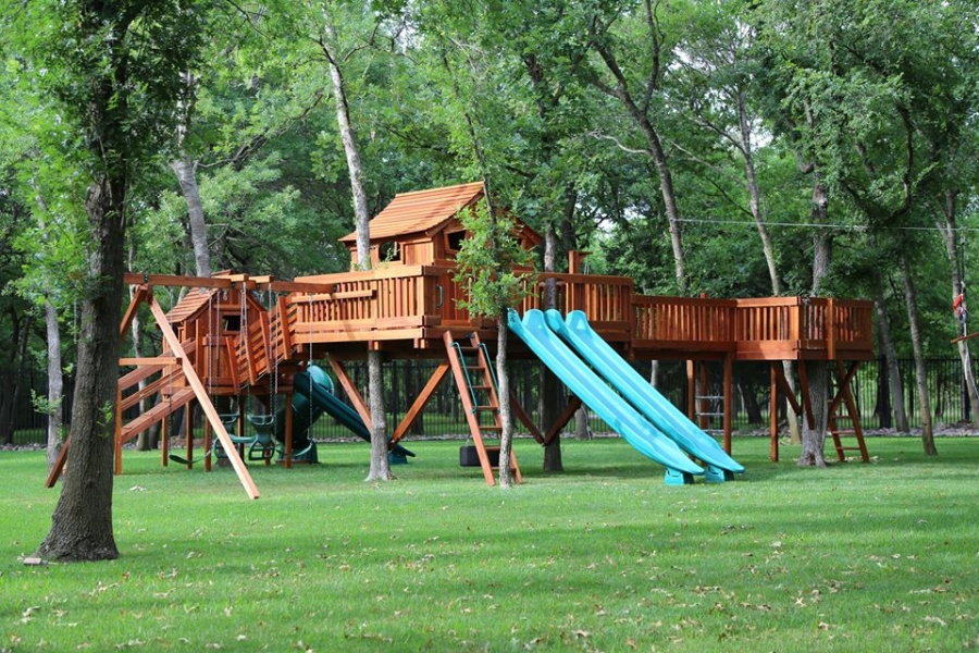 Tree fort bridged to tree deck with a monkey bar bridge. Fun Shack bridge to tree fort with an angle bridge. Slide and swing accessories on this outdoor playset.