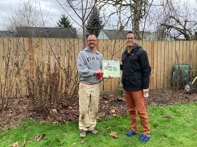 Two people standing in front of pruned bushes and a fence, holding their certification sign.