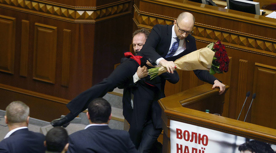 Rada deputy Oleg Barna removes Prime Minister Arseny Yatseniuk from the tribune, after presenting him a bouquet of roses, during the parliament session in Kiev, Ukraine, December 11, 2015. REUTERS/Valentyn Ogirenko      TPX IMAGES OF THE DAY