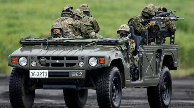Japanese Ground Self-Defense Force soldiers ride on a high-mobility multipurpose wheeled vehicle (Humvee) during an annual training session near Mount Fuji at Higashifuji training field in Gotemba, west of Tokyo, August 19, 2014. REUTERS/Yuya Shino (JAPAN - Tags: MILITARY POLITICS) - RTR42W6E