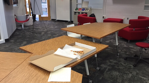 An almost-empty pizza box sitting on a table.