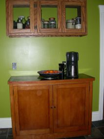 Open shelving replaced with a hanging cabinet from the Re-Store and a kitchen cabinet found on Craigslist that was lovingly restored into an Entertainment Center, and returned to its home the kitchen.