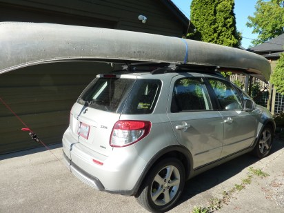 The wee little Suzuki loaded up with the ginormous canoe.