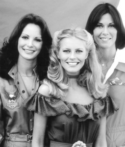 Three women dressed in 70s clothes, staring challengingly into the camera (& smiling).