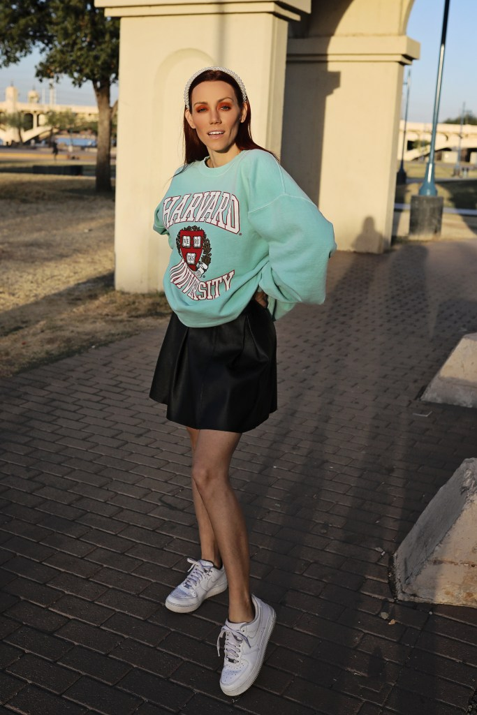 style a sweatshirt with a pleated skirt
