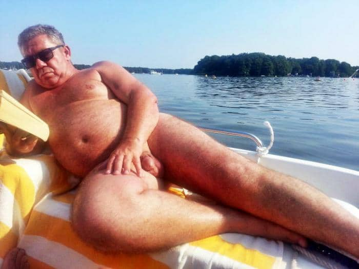 Bold naked granddad reading naked on his boat