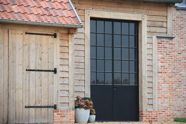 Zwart aluminium voordeur in contrast met houten