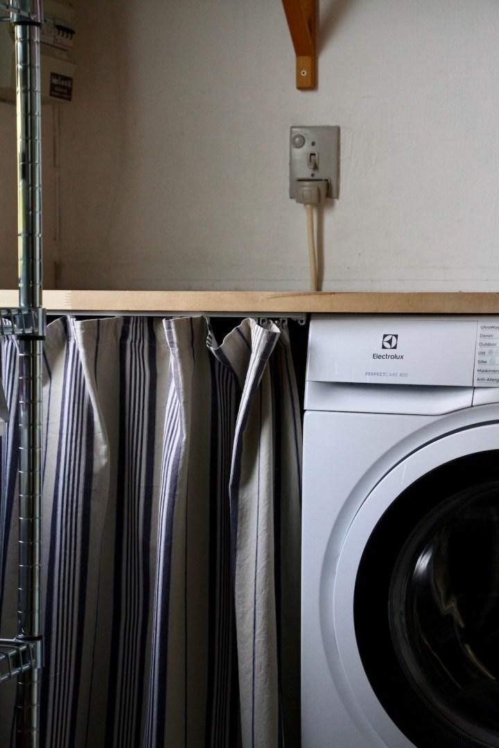 Bryggers med forhæng foran vasketøjskurven