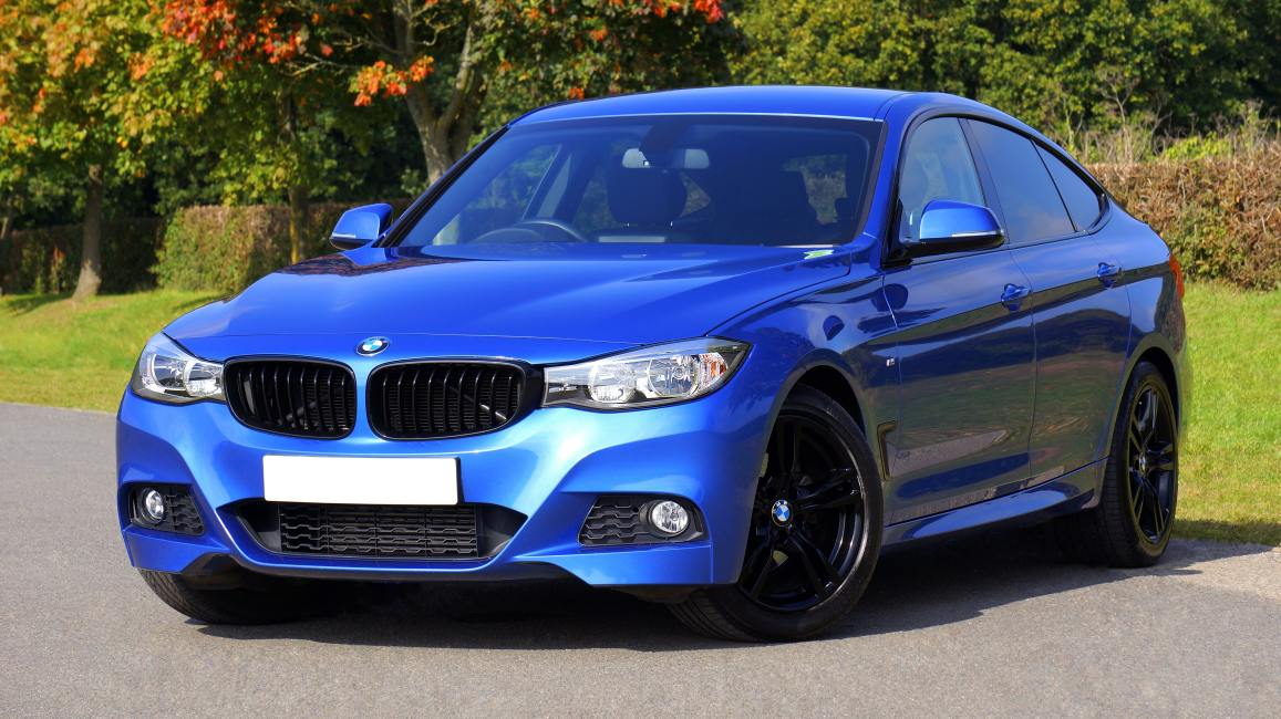 blue-bmw-sedan-near-green-lawn-grass-170811