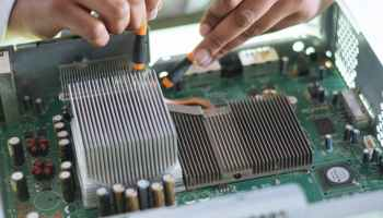 crop technician checking contacts on motherboard in workshop