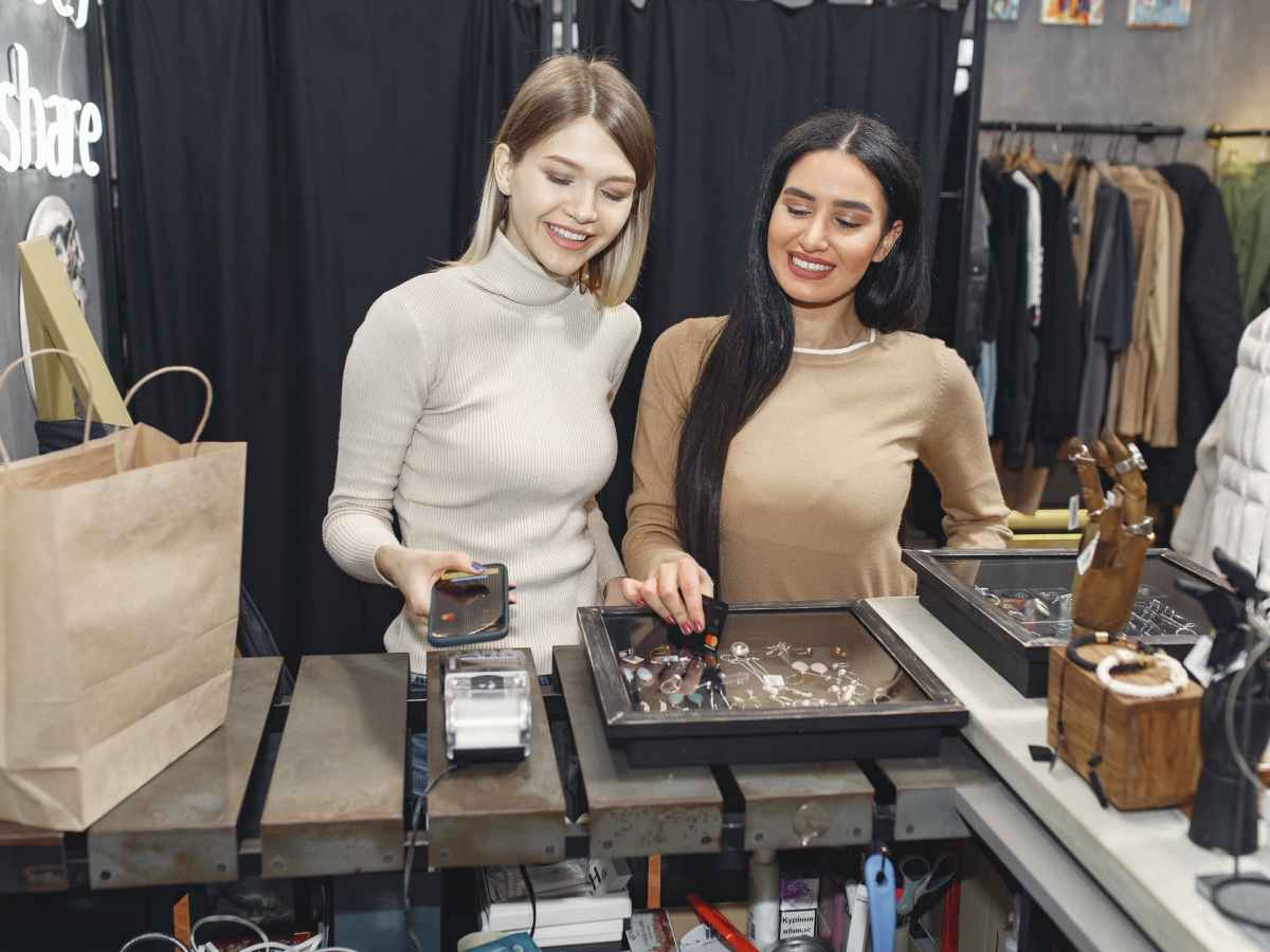 girlfriends paying with smartphone for purchases