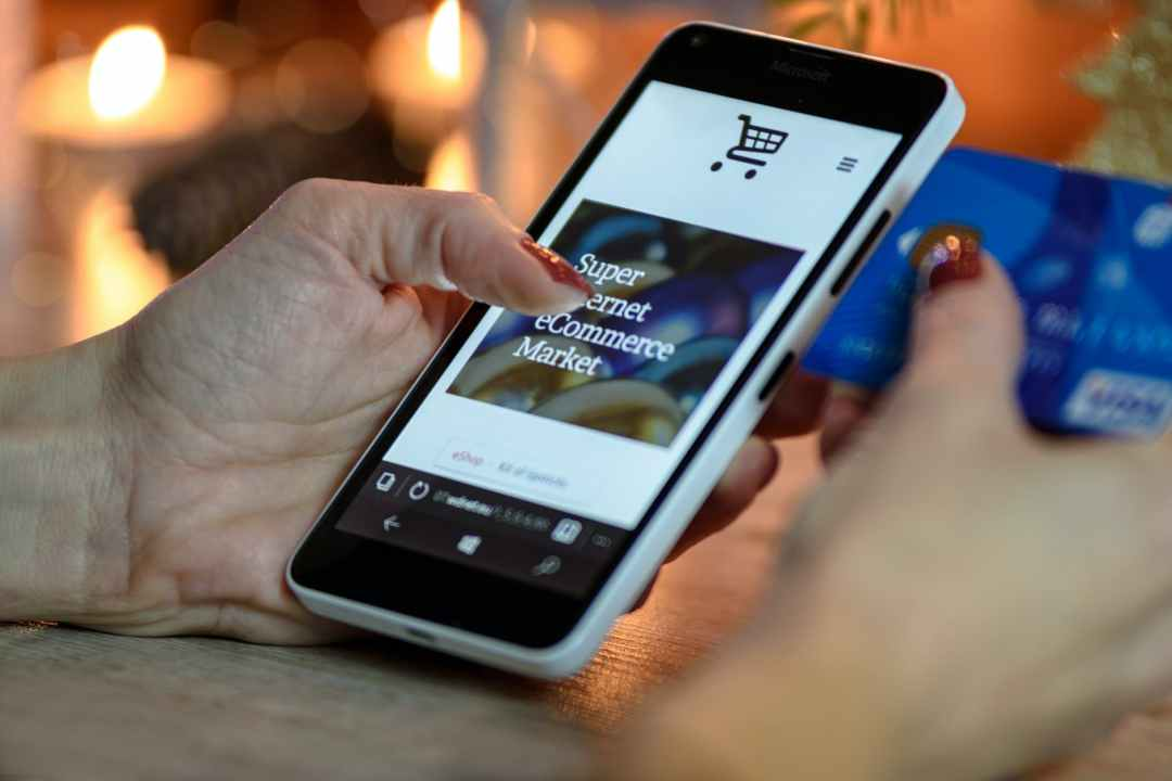person using black and white smartphone and holding blue card