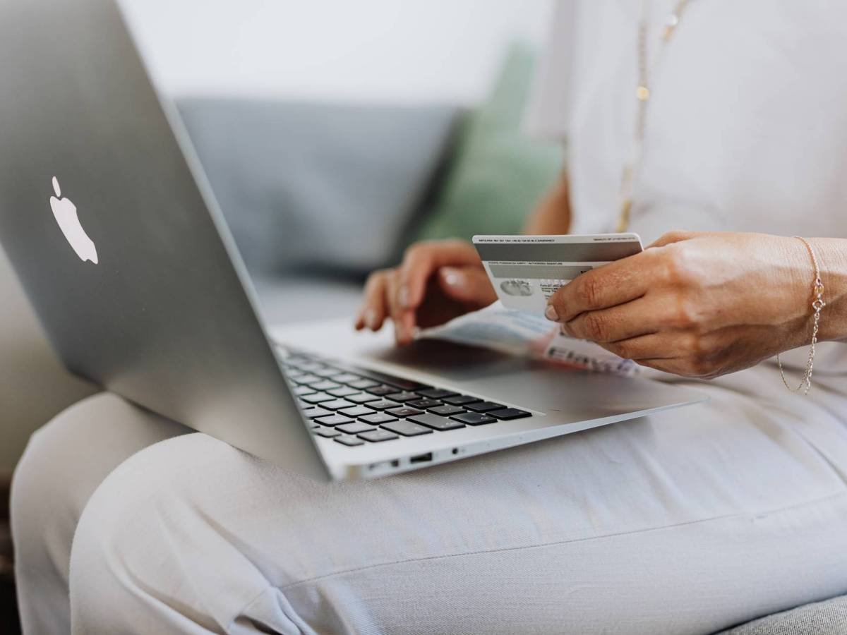 person using a macbook and holding a credit card