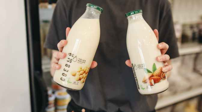 person holding bottles with milk