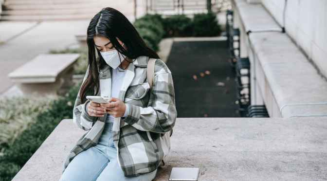 lady sitting on fence with phone and tablet in mask