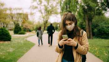 woman in brown leather jacket using smartphone