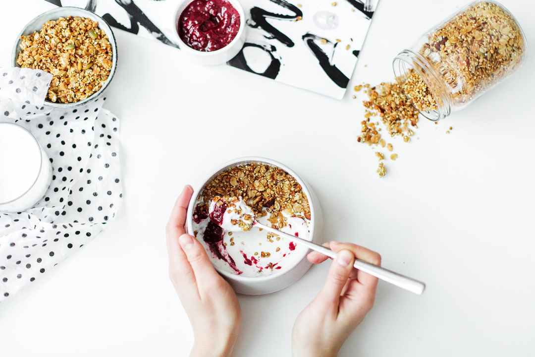 person mixing cereal milk and strawberry jam on white ceramic bowl