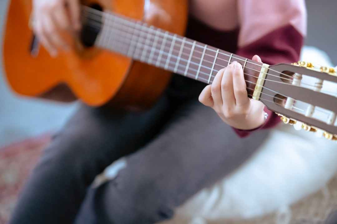 unrecognizable woman playing guitar in room
