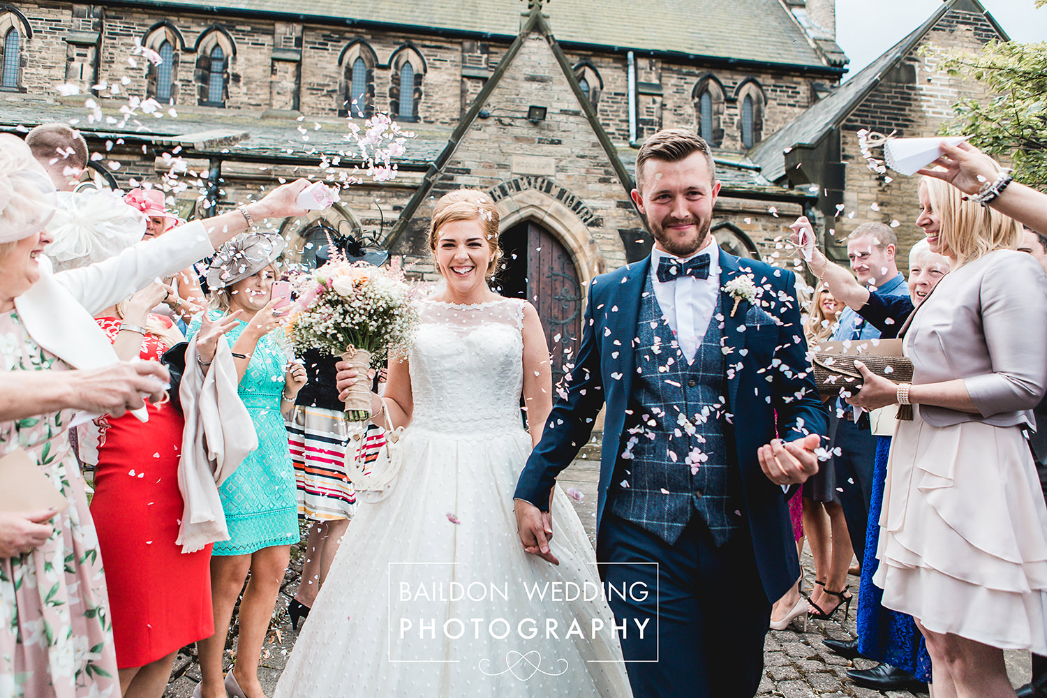 Newlyweds are showered with confetti by guests outside the church on their Leeds wedding Yorkshire