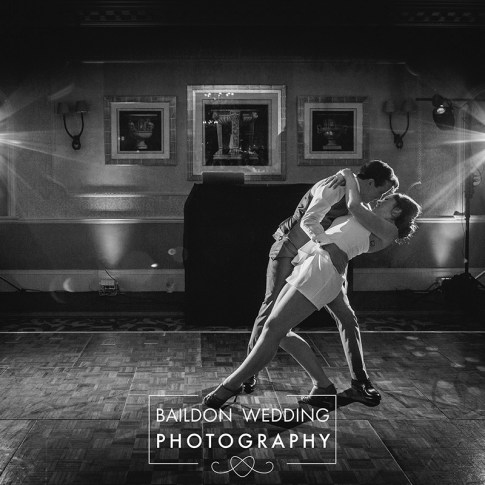 Bride and groom have choreographed first dance, bride wears short bridal outfit during Wood Hall wedding.