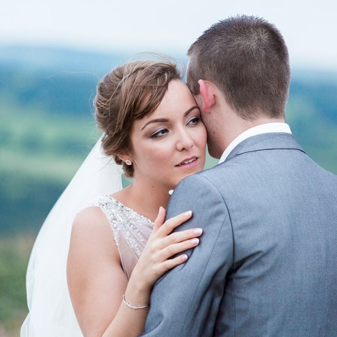 Groom gently kisses bride as she looks into the distance overlooking fields and moorland rural Yorkshire wedding