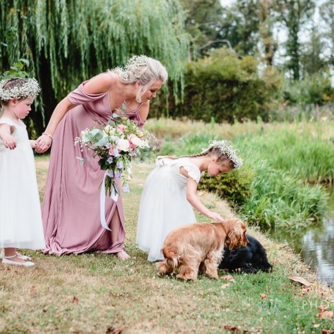 Flower girls and puppies at lakeside outdoor wedding in France