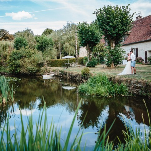 Bride and groom stood by the lake at the manoir de la Foulquetiere wedding venue in the Loire Valley region of France