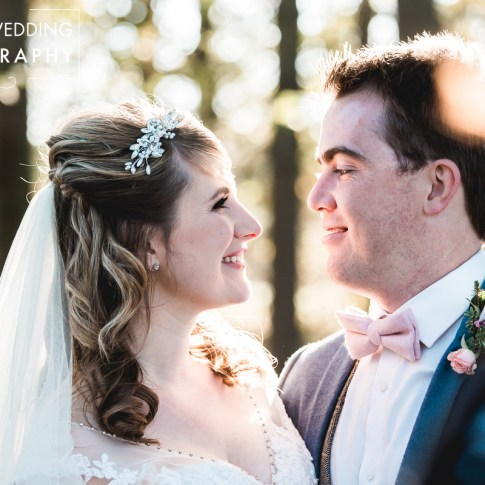 Bride and groom looking into each other's eyes in the woodland surrounding Sandburn Hall wedding venue in York