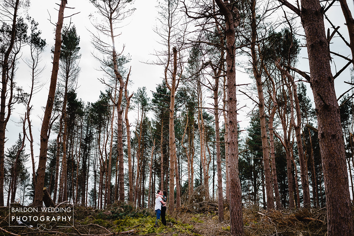 couple stood amongst tall trees at woodland in Bingley West Yorkshire