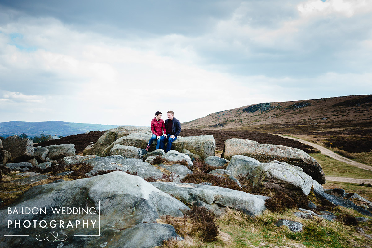 couple sat on rocks at the top of Ilkley moor in West Yorkshire, views of hills behind