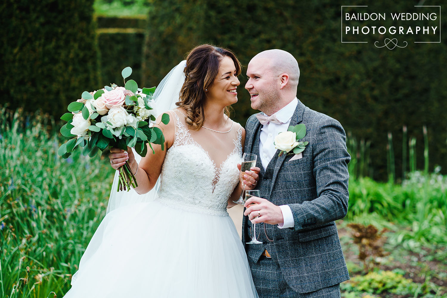 Couple laughing holding champagne in walled garden