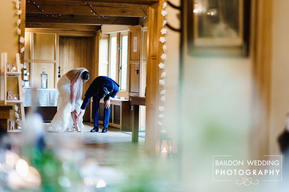 Brides garter falls down her leg, groom helping her