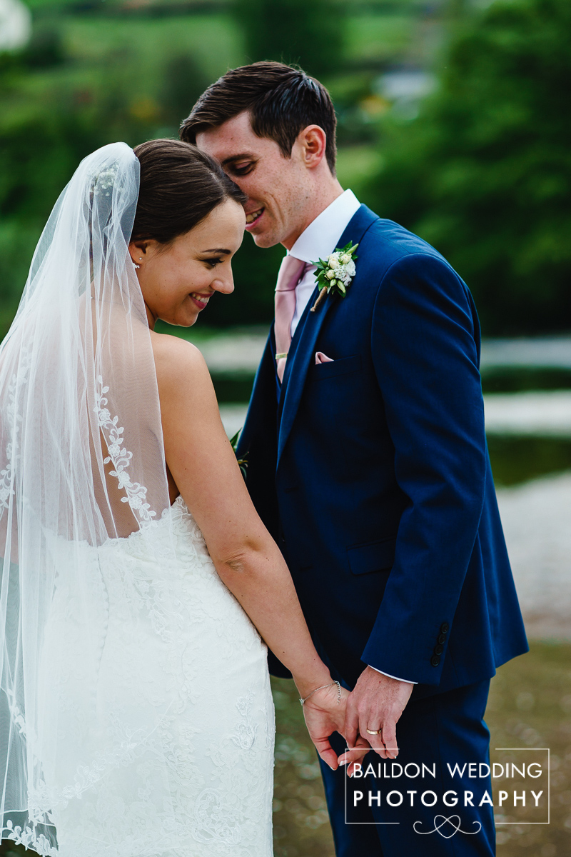 Wedding photograph of couple holding hands as he whispers
