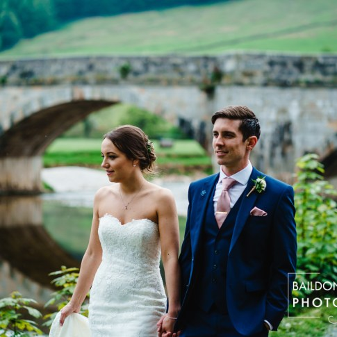 Bride and Groom outside The Red Lion Burnsall wedding venue with Burnsall bridge in background