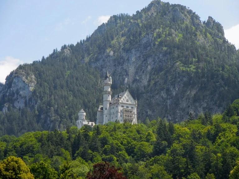 Schloss Neuschwanstein sits atop a hill in front of a mountain