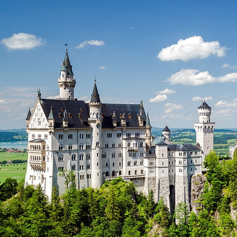 fairytale castle with turrets and towers sits on a German cliffside Schloss Neuschwanstein